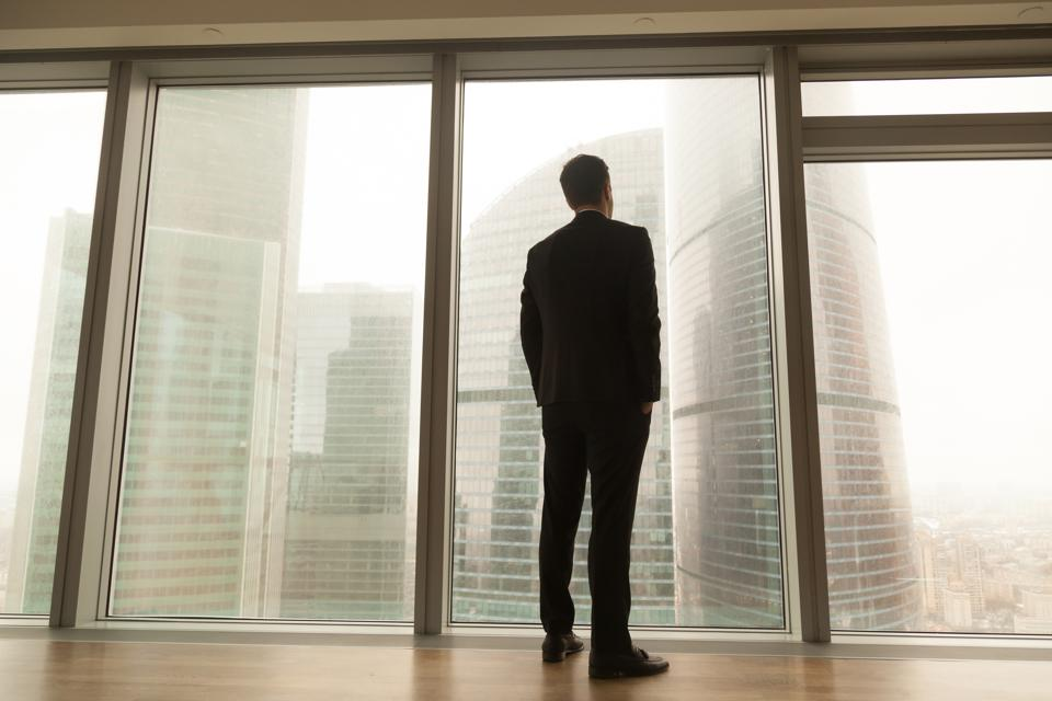 businessman looking out of the window thinking about race equality