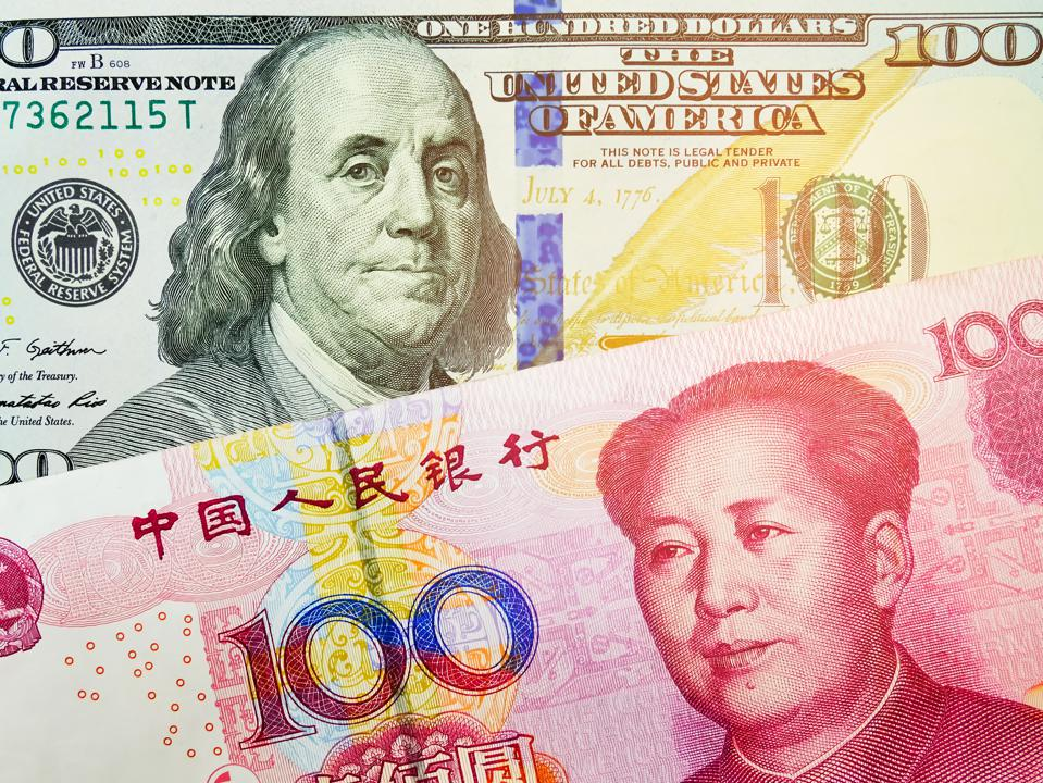 Close up view of US Dollar and Chinese yuan bills. currency exchange rate.