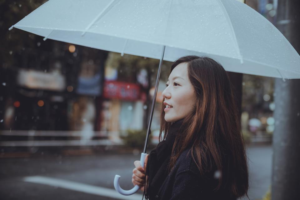Young woman holding umbrella and walking along city street in the snow