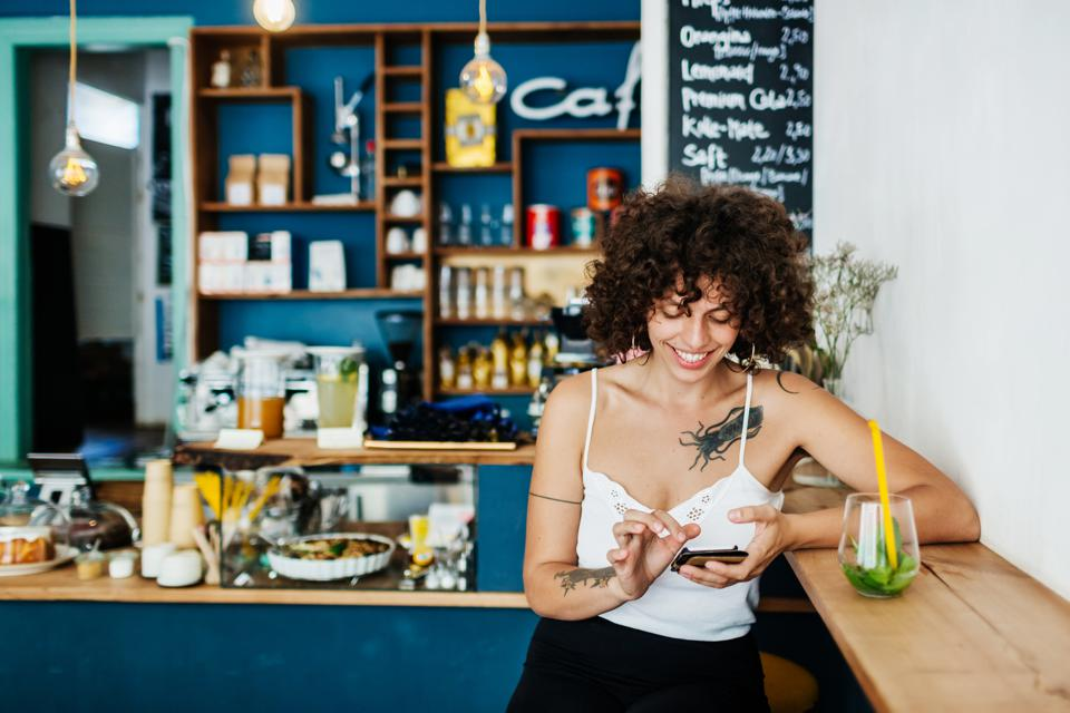 Tattooed Woman Using Smartphone In Colourful Cafe