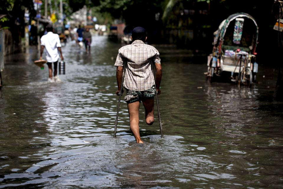 A disabled man traveling through a flooded area of...