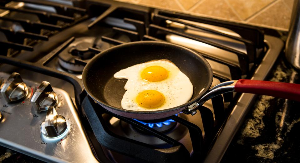 Two eggs being fried in a non-stick skillet on a gas range.