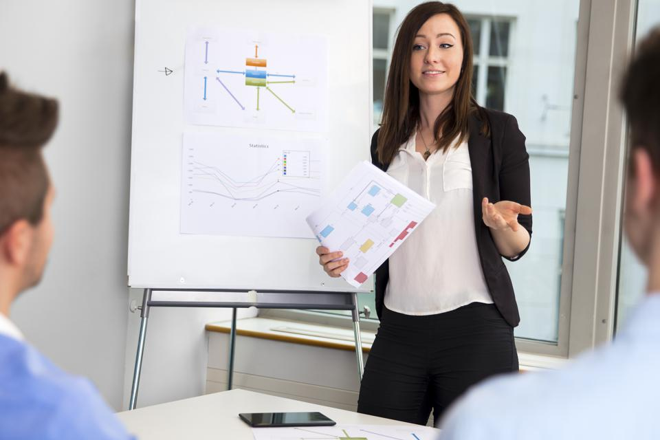 Businesswoman Holding Chart While Communicating With Colleagues