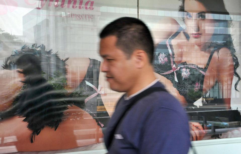 A man walks past a lingerie advertisemen