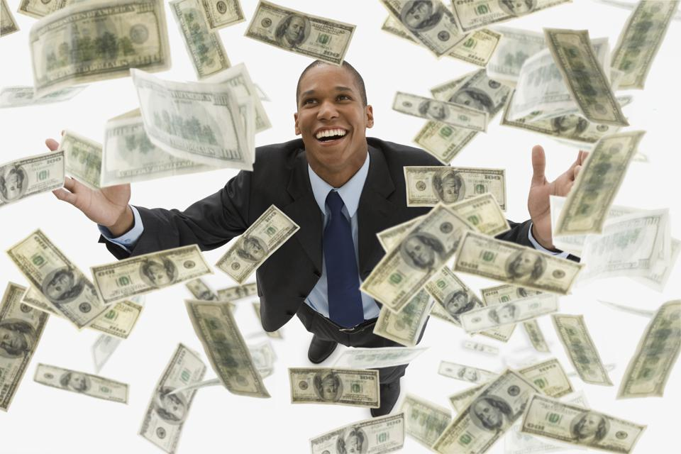 Mixed race businessman catching falling 100 dollar bills
