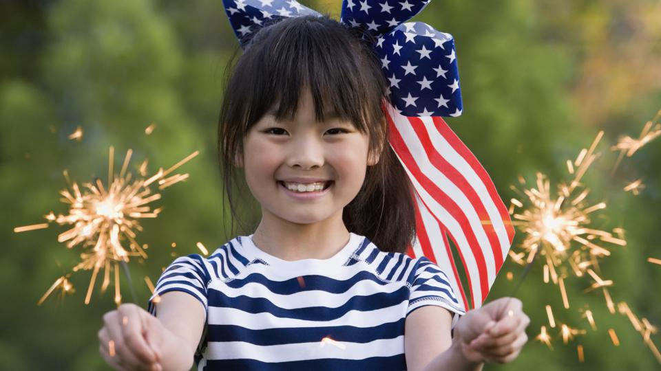 Asian girl holding sparklers on Fourth of July