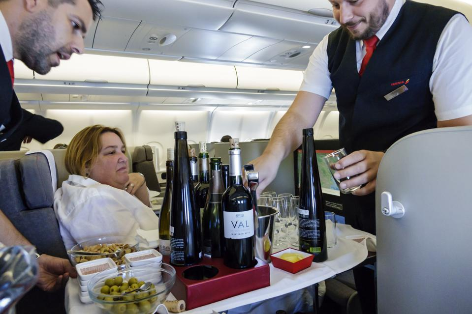 Commercial airliner jet attendants serving wine in the business class cabin of Iberia flight 6165.