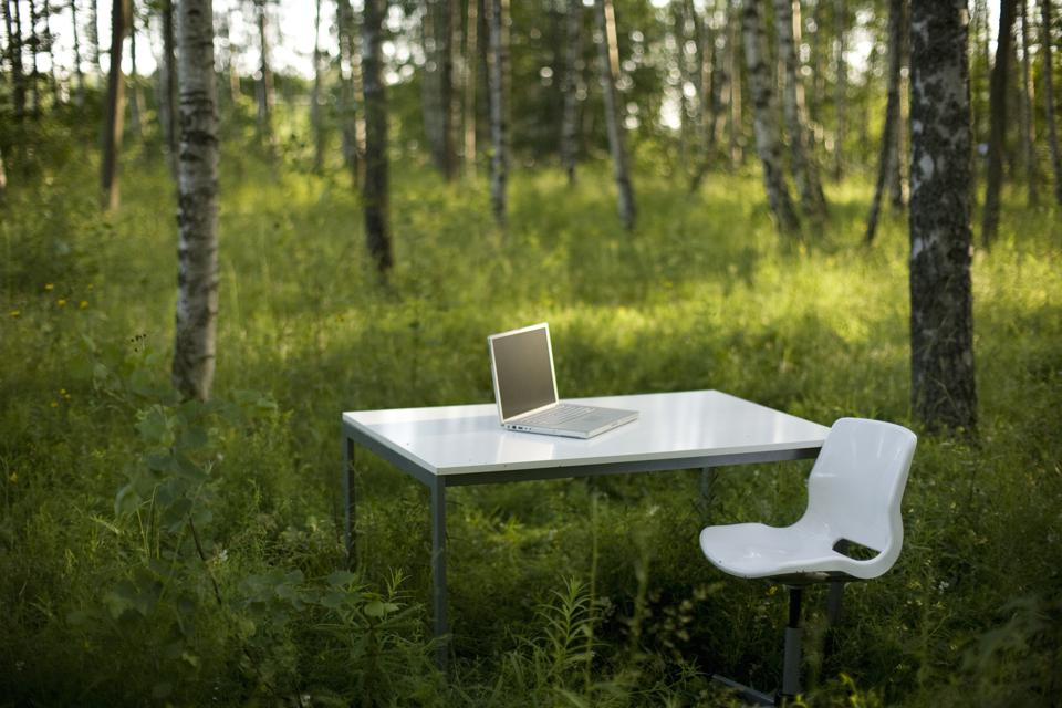 A computer on a white desk in a forest Sweden.