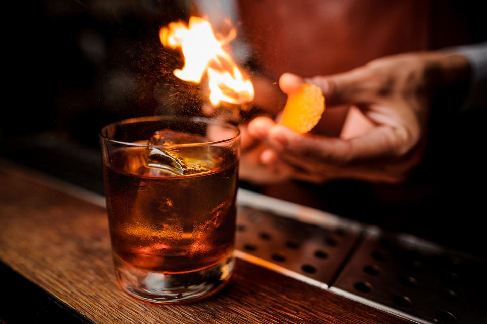 The bartender makes flame above cocktail close up