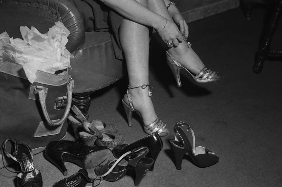 A woman trying on a selection of shoes, 1951.
