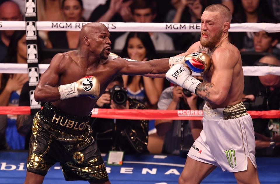 Floyd Mayweather Jr. punches Conor McGregor.