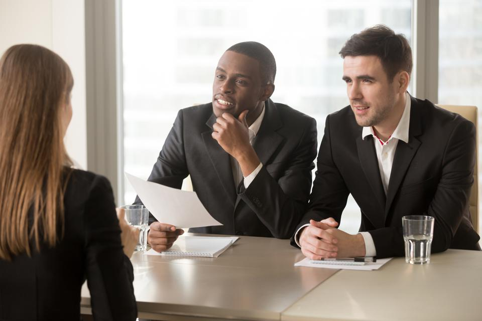 Hiring managers examining female job candidate