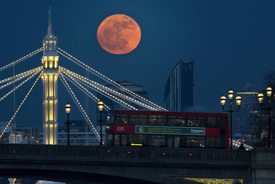 The full moon appears red as it rises behind Albert bridge (illuminated, rear) and Battersea Bridge (foreground) on the river Thames. (Photo by Anthony Devlin/PA Images via Getty Images)