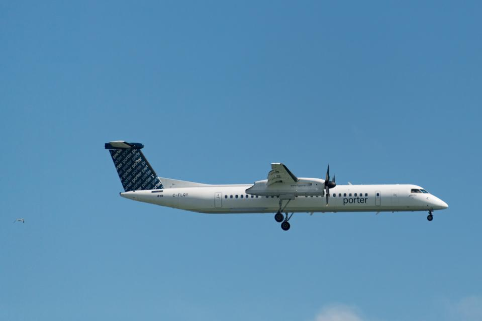 Porter Airlines aeroplane flying in the air, the sleek white...coronavirus travel COVID-19