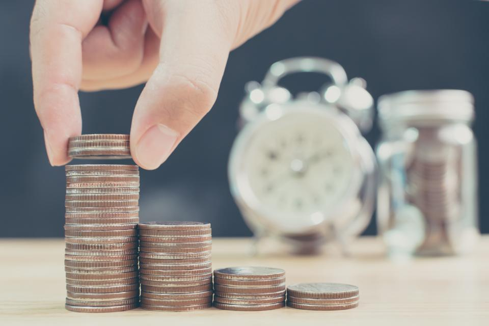 Hand of male or female putting coin stack step up increase save money with blurred clock and jar background, Finance and investment concept