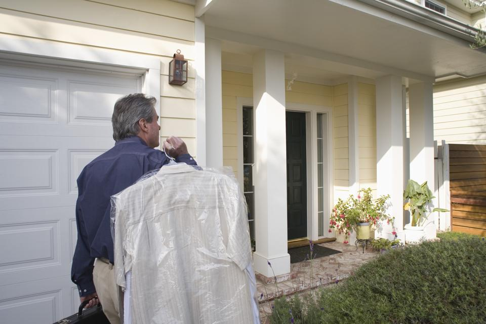 Man walking into home carrying dry cleaning