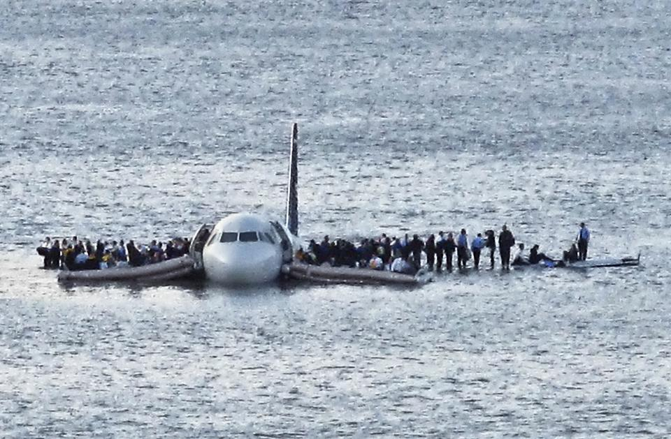 Passengers wait to be rescued on the wings of a US Airways Airbus 320 jetliner that safely ditched in the frigid waters of the Hudson River in New York, Jan. 15, 2009, after a flock of birds knocked out both its engines.