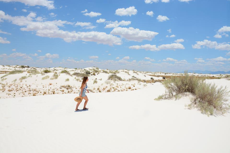 Girl hiking on beautiful white sand dunes in New Mexico.