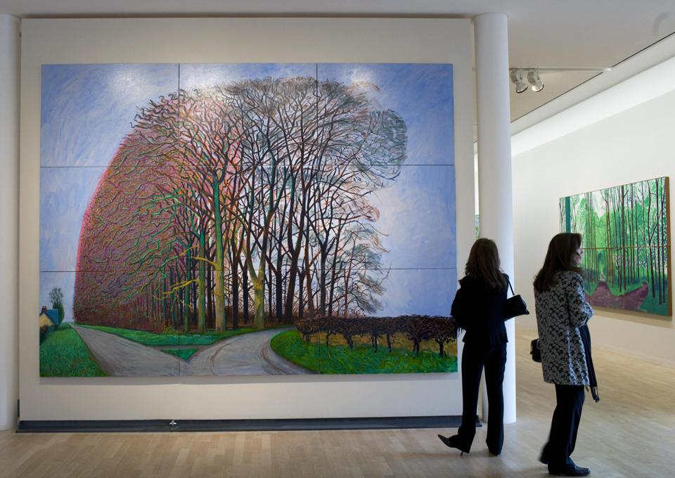 Visitors stand next to a painting by Bri