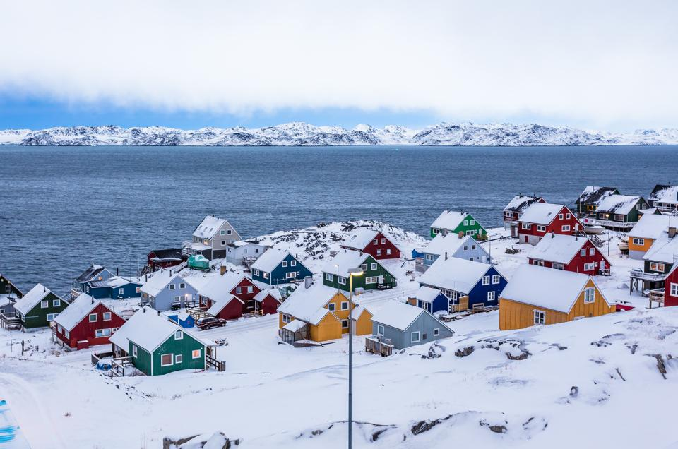 Colorful houses among rocks and snow at the fjord in a suburb of Nuuk, Greenland