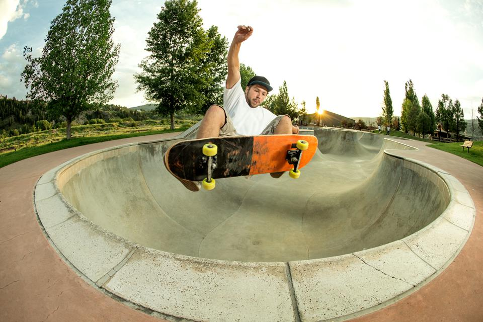 Kid with a snowboard jumping out of a skate park bowl.