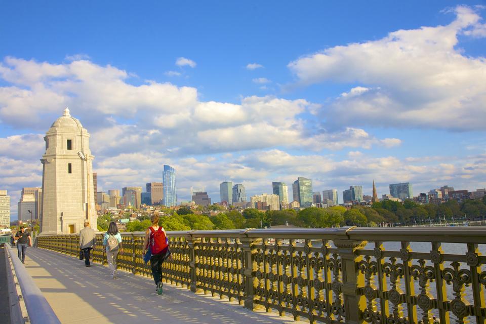 People walking across Salt and Pepper Bridge with Boston in distance