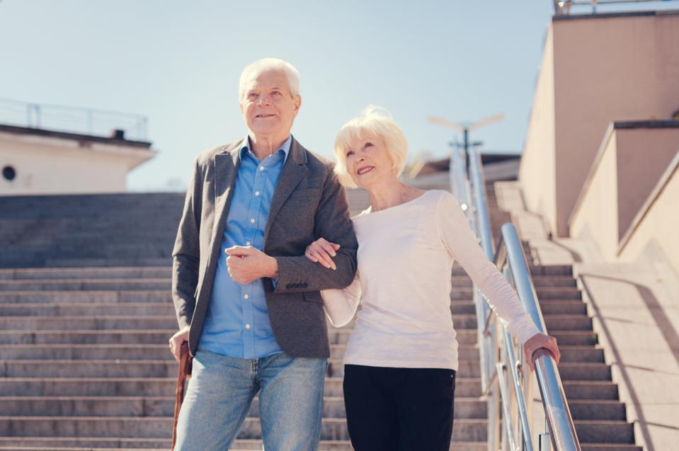 Pleasant elderly couple going down the stairs arm in arm