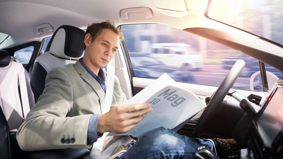 Caucasian driver reading magazine in autonomous car. Self driving vehicle. Driverless car.