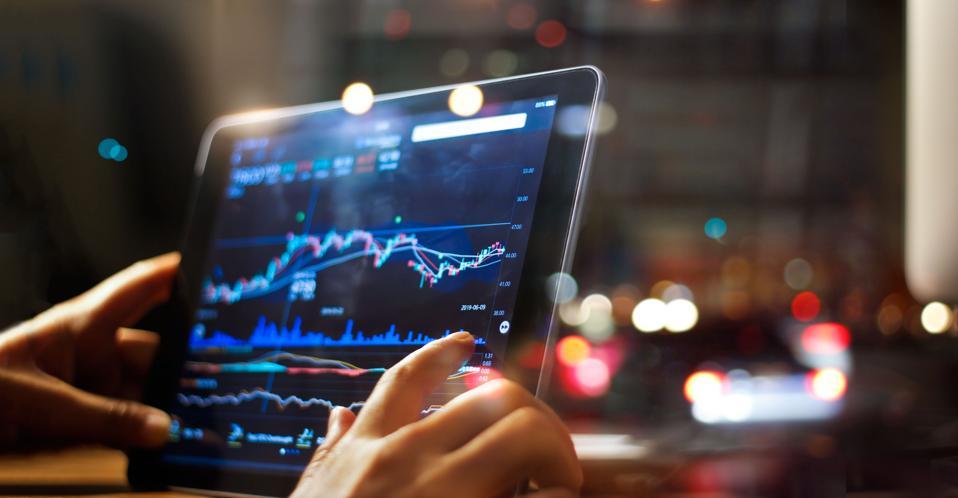 Businessman checking stock market data on tablet