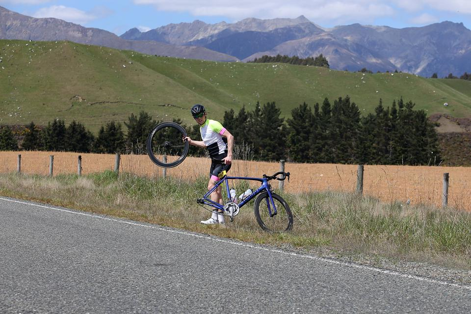 Cyclist on the side of the road with a flat tire.