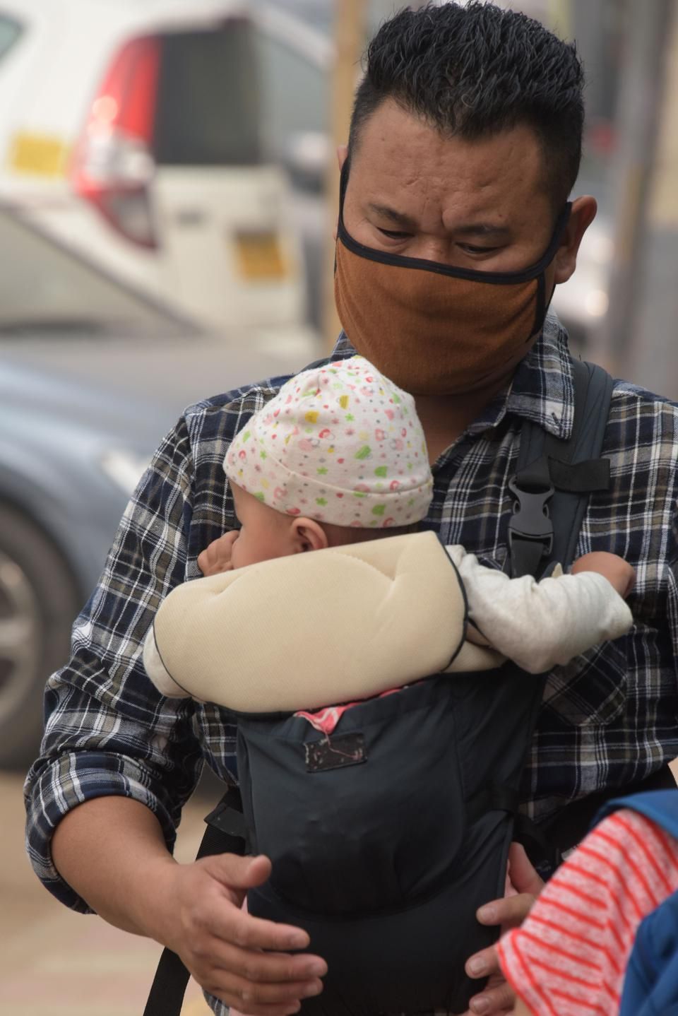 Adult wearing mask; infant in carrier.