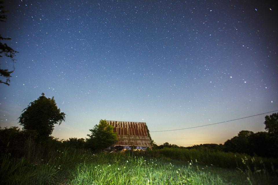The starry sky above the barn at the farm at night