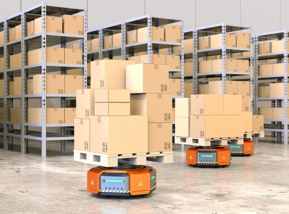 Oranssit robottikuljetusalukset, jotka kuljettavat kuormalavoja tavaroiden kanssa modernissa varastossa