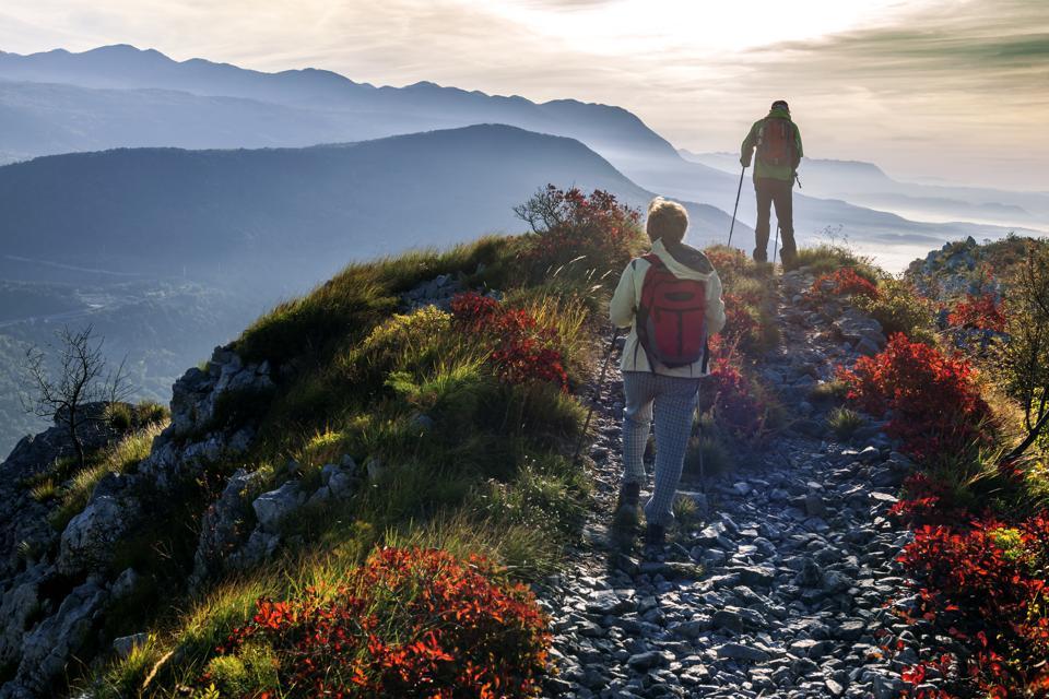 Happy Senior Couple Hiking at Autumnal Dawn in Julian Alps, Slovenia, Europe