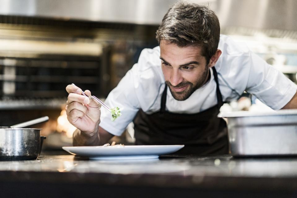 Male chef garnishing food in kitchen