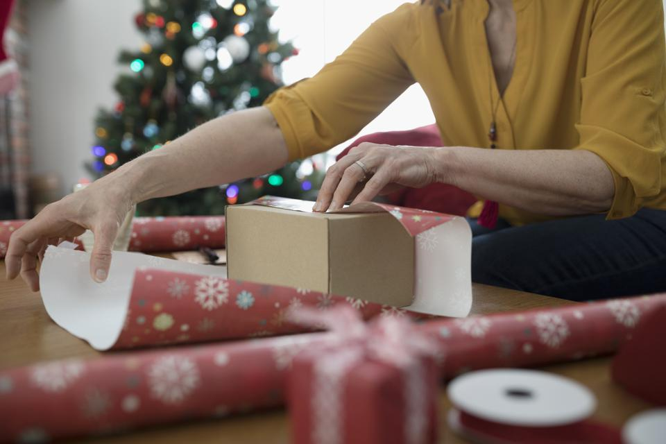 Woman wrapping Christmas gift with wrapping paper
