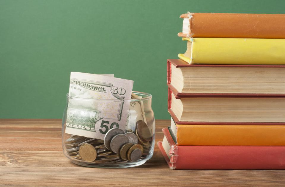 Coins in glass jar and stack of books on wooden table.
