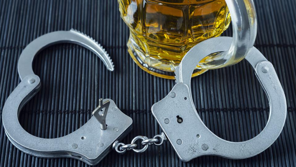 Alcohol addiction. Handcuffs and a glass of beer. Symbolic image of alcoholism.