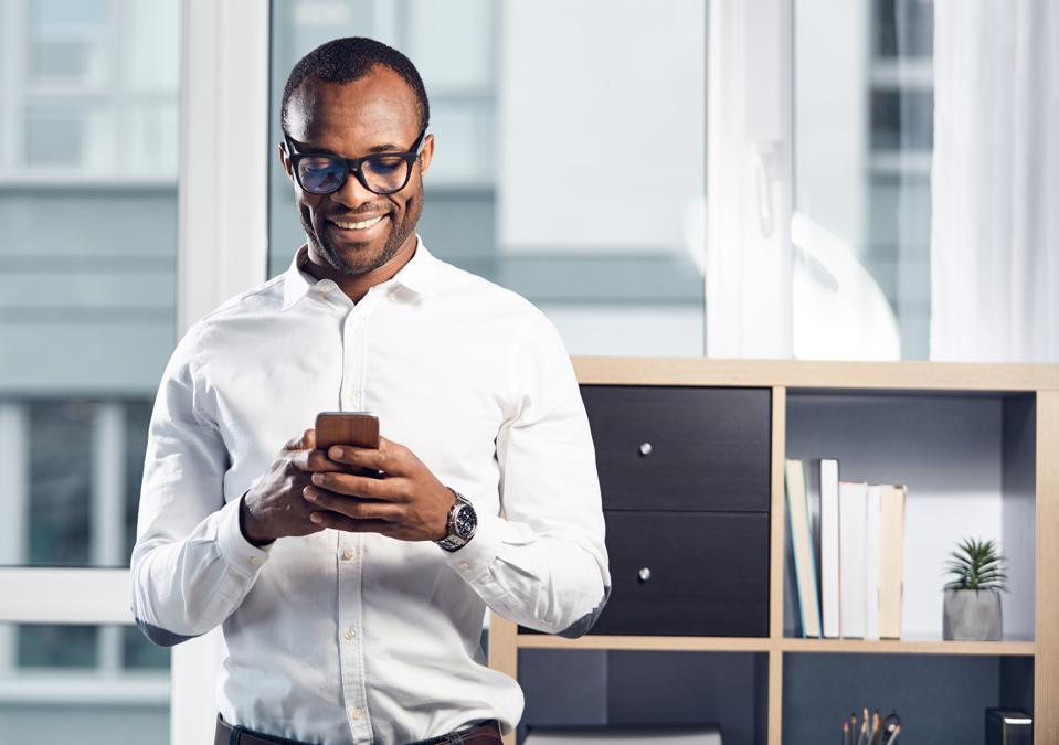 Cheerful stylish businessman is using his smartphone