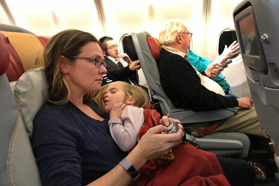 A mother and daughter during a flight from New York to Rome.