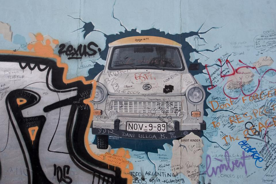 East Side Gallery wall picture featuring a Trabant, a characteristic car brand of East Germany, with the date of the wall collapse on the registration number.
