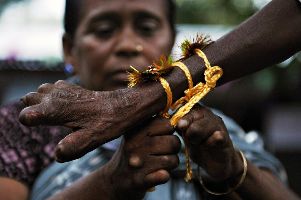 An Indian girl ties a 'rakhi' (sacred th