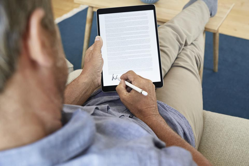 Mature man signing digital contract on tablet