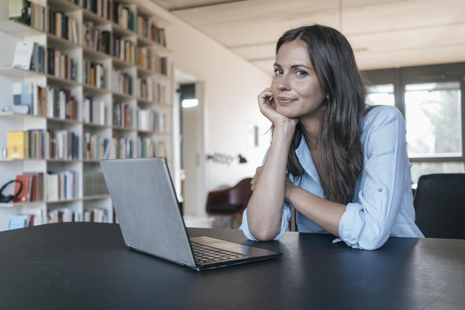 Portrait of smiling woman sitting at table with laptop