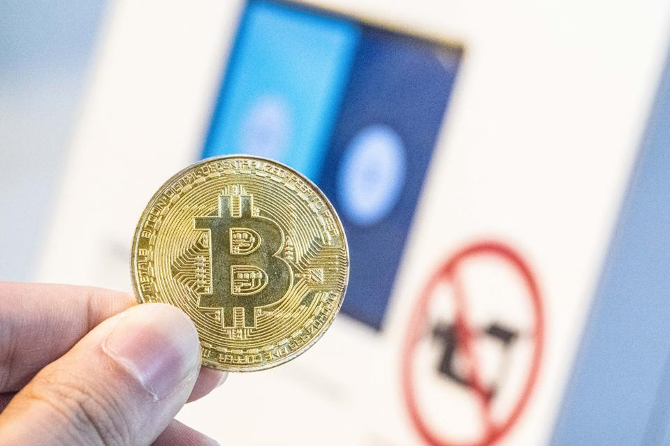 A young man is purchasing digital Cryptocurrency, Bitcoin with the HK bitcoin ATM