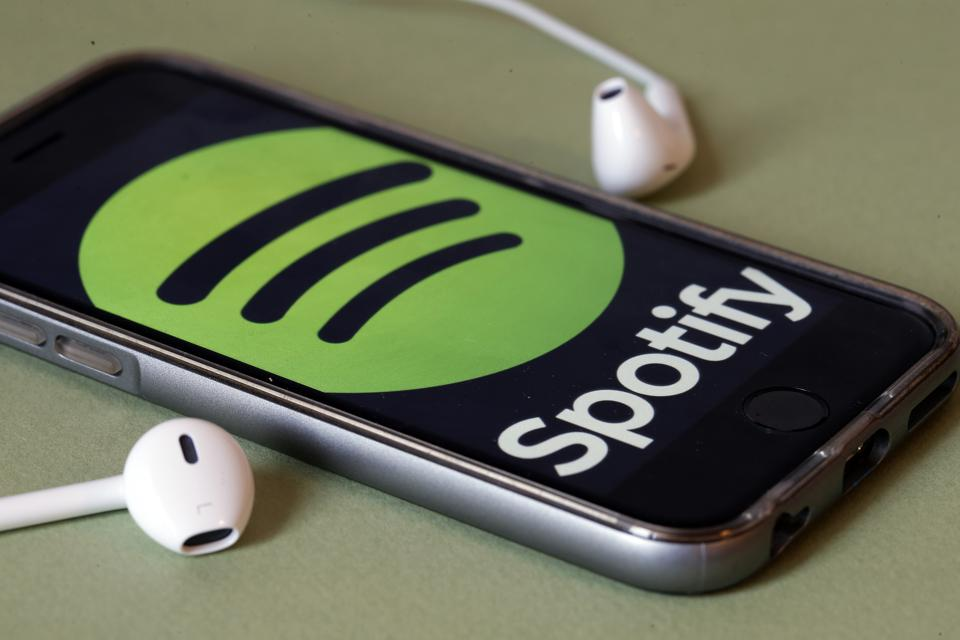 Spotify logo on a smartphone with earphones