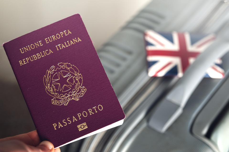 An Italian passport pictured next to a suitcase.
