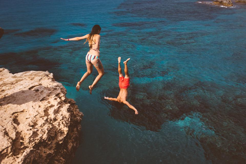 Active couple diving from high cliff into ocean