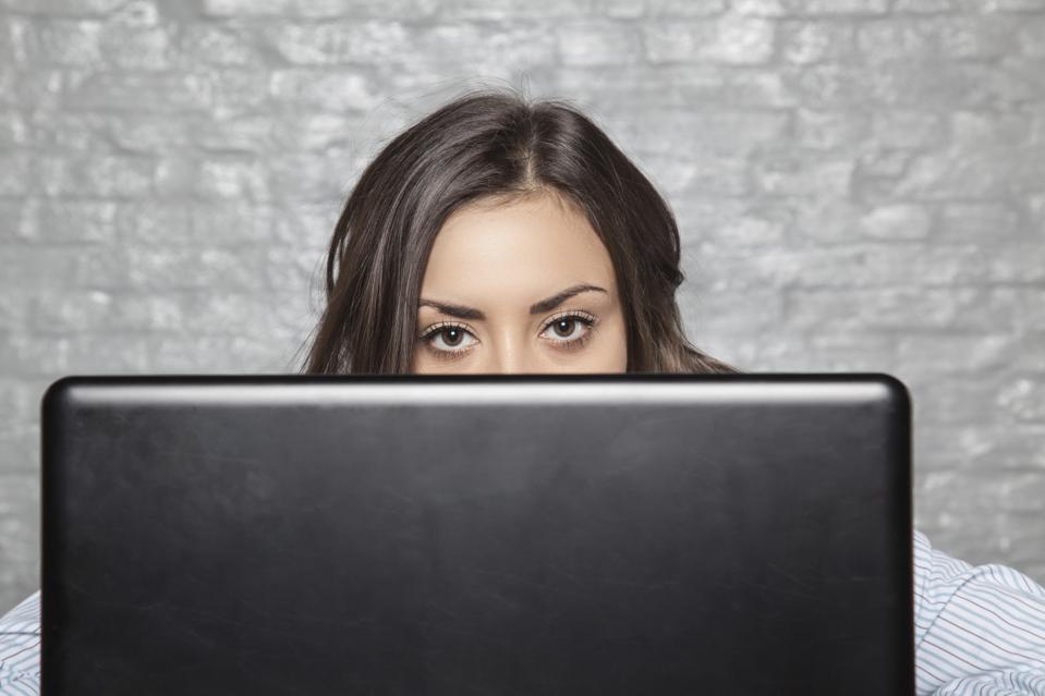 photo: a young secretary hides behind her monitor