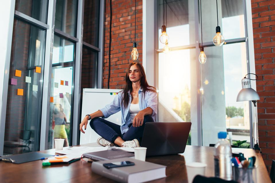 Young businesswoman meditating sitting on working table in lotus pose in her office